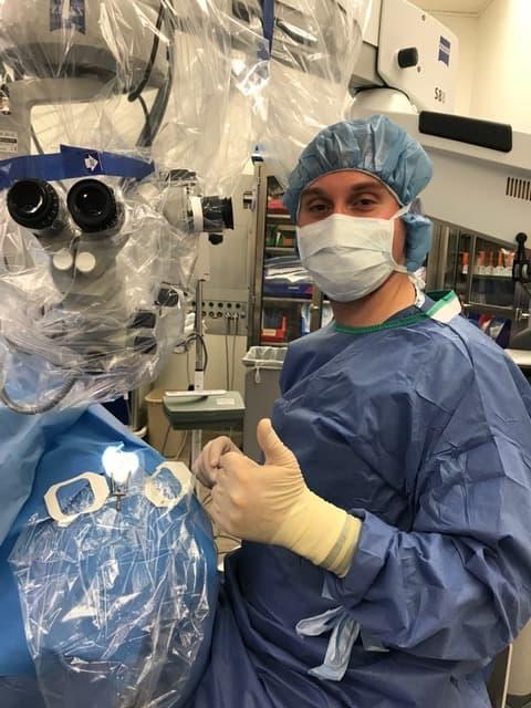 Cataract surgeon in scrubs standing in front of equipment